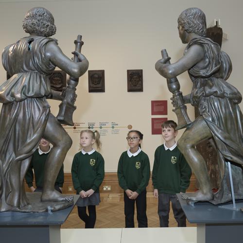 School children looking at bronze Wolsey Angles sculptures