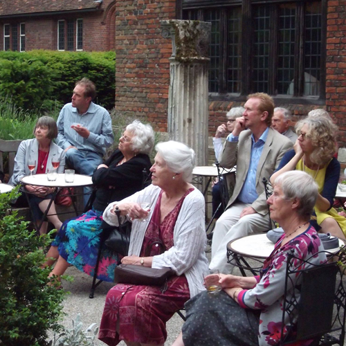 People sitting in courtyard, drinking tea and listening to someone talk