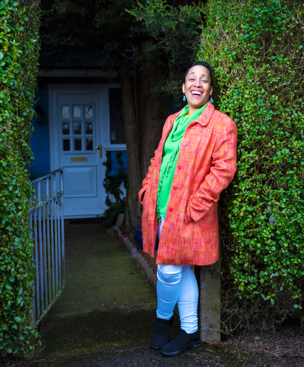Woman in pink coat leaning against a green hedge
